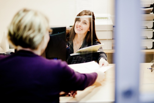 A lady at a desk takes paperwork from a client